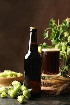 Bière, houblon et blé sur table en bois contre brown