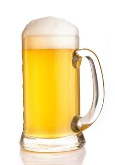 Bière légère dans un verre avec de la mousse sur fond blanc