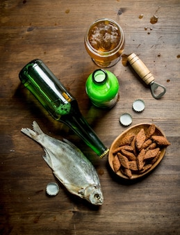 Bière avec des miettes dans un bol et du poisson séché. sur fond de bois