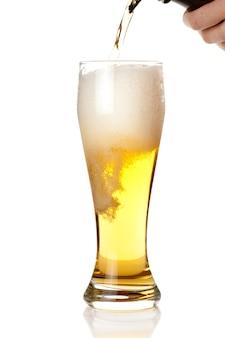 Bière avec de la mousse en verre isolé on white