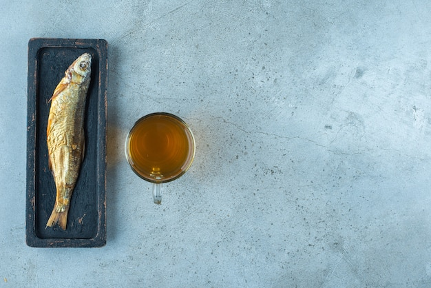 Une bière en verre à côté du poisson sur une assiette en bois, sur la table bleue.