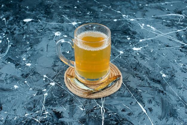 Une bière en verre et du poisson sur un dessous de plat, sur la table bleue.