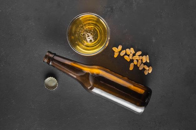 Bière vue de dessus avec des cacahuètes sur la table