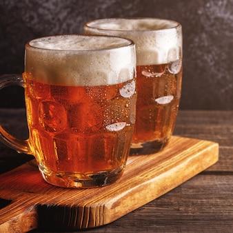 Bières froides en verre avec des copeaux sur une surface sombre