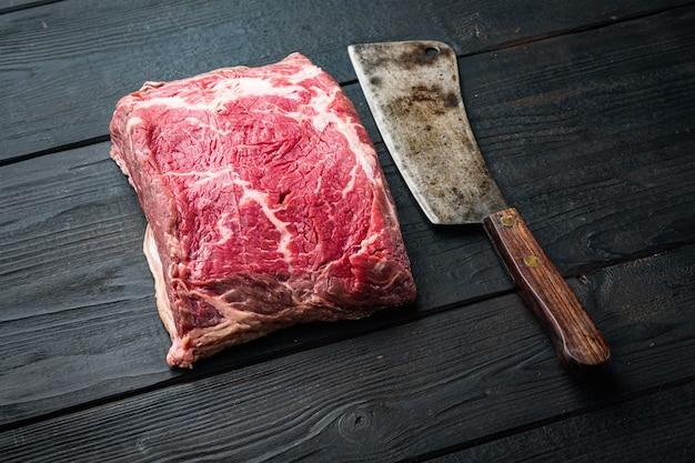 Bifteck de boeuf biologique brut de kansas city coupé, sur table en bois noir