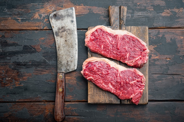 Bifteck de boeuf biologique brut de kansas city coupé, sur la vieille table en bois, vue du dessus, avec copie espace pour le texte