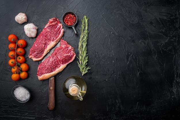 Bifteck de boeuf biologique cru de kansas city coupé, sur table noire, vue du dessus