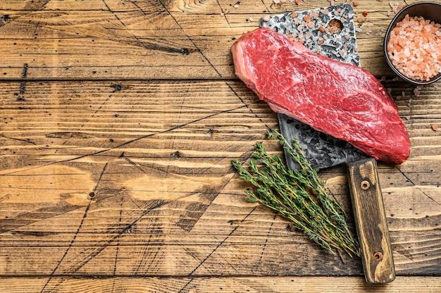 Bifteck de contre-filet cru sur couperet à viande, bœuf marbré
