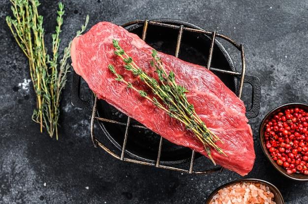 Bifteck de contre-filet cru sur un grill, boeuf marbré