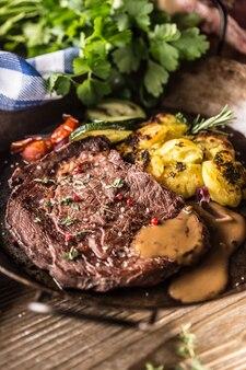 Bifteck de faux-filet de boeuf juteux pommes de terre rôties avec sauce légumes grillés sel poivre et herbes dans une poêle vintage.