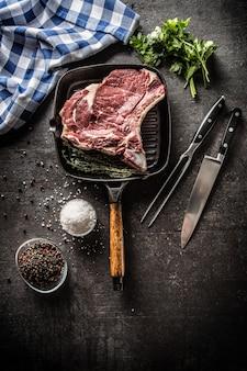 Bifteck de faux-filet dans une poêle à griller avec une fourchette et un couteau aux herbes sel poivre.