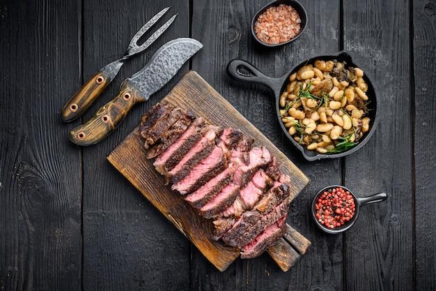 Bifteck de faux-filet grillé en tranches de boeuf marbré rare sur une planche de service en bois avec des haricots blancs
