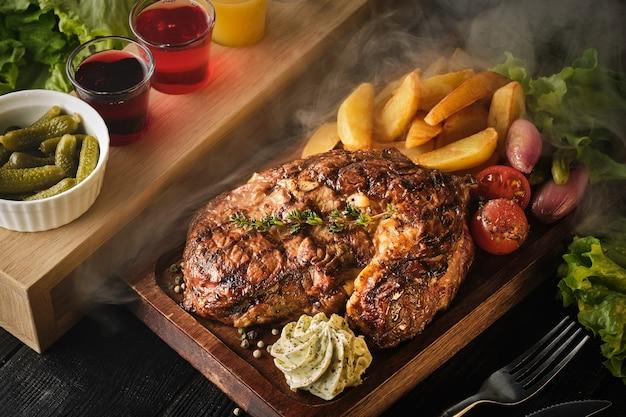 Bifteck de faux-filet avec pommes de terre, oignons et tomates cerises au four. steak juteux au beurre aromatisé