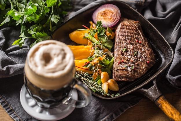 Bifteck de flanc de boeuf dans une poêle à griller avec une décoration aux herbes à l'ail et à la purée de batata et de la bière pression.