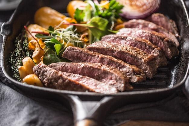 Bifteck de flanc de boeuf dans une poêle à griller avec une purée de batata à l'ail et une décoration aux herbes.