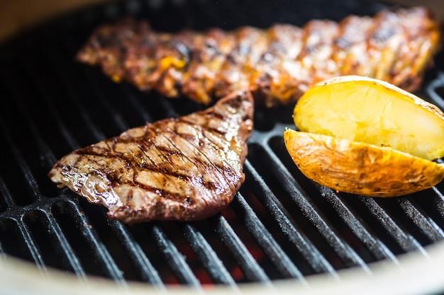 Bifteck de flanc de boeuf en gros plan cuisant sur le gril.