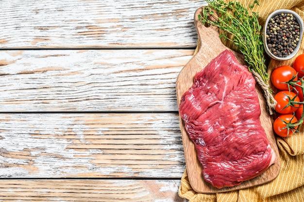 Bifteck de flanc frais sur une planche à découper.