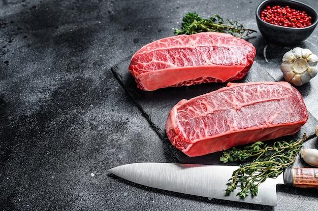 Bifteck de lame supérieure cru vieilli à sec sur une planche de pierre