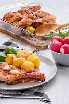 Bifteck avec os et pomme de terre au four dans une rôtissoire à l'ail et au thym