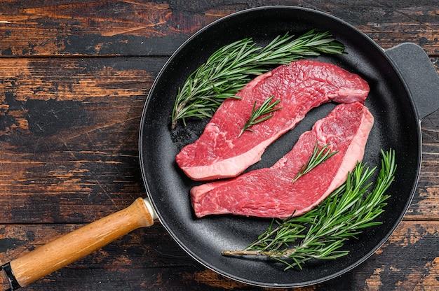 Bifteck de rumsteck de viande de boeuf cru dans une casserole.