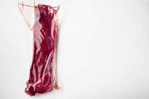 Bifteck de surlonge dans un emballage sous vide. ensemble de packs de marché, sur table en pierre blanche, vue de dessus à plat