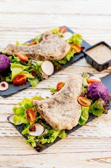Bifteck de viande de porc barbecue grillé sur une plaque noire avec des légumes