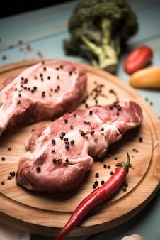 Biftecks crus à angle élevé sur planche de bois avec du poivre et du brocoli