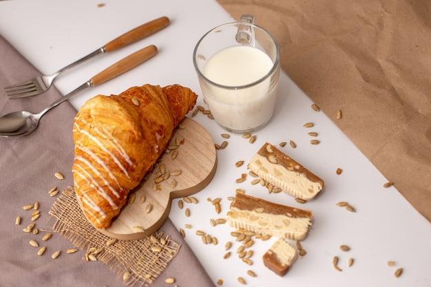 Big croissant, un verre de lait et des tranches de sorbet sucré.