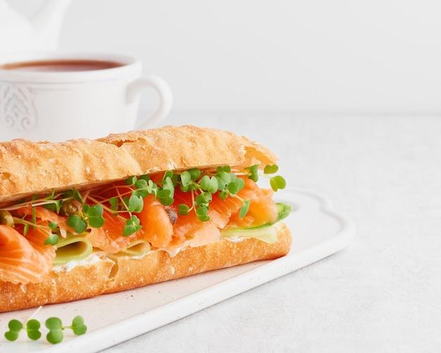 Big sandwich au saumon, fromage à la crème et tranches de concombre sur table en béton blanc