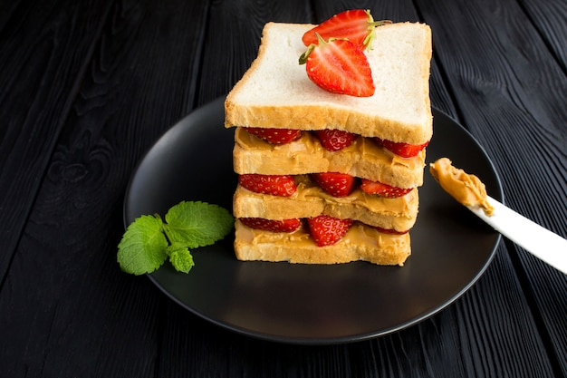 Big sandwich aux fraises et beurre d'arachide sur la plaque noire