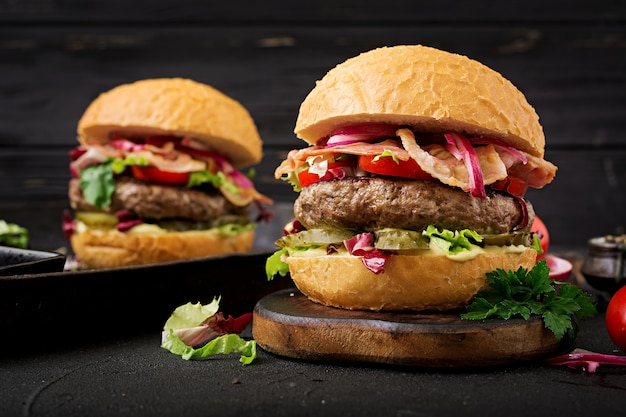 Big sandwich - hamburger hamburger avec du boeuf, de la tomate, du concombre mariné et du bacon frit.