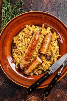 Bigos chou cuit aux champignons et saucisses de viande sur une assiette