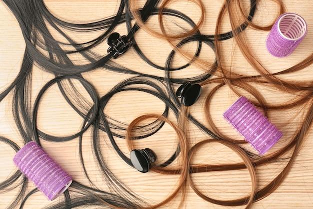 Bigoudis avec des mèches de cheveux sur une table en bois