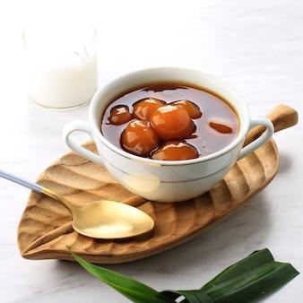 Biji salak kabocha (ou candil) est un dessert indonésien célèbre pendant le petit-déjeuner du ramadan. fabriqué à partir de boules de kabocha de patate douce ou de citrouille jaune avec du sirop de sucre de palme et du lait de coco.