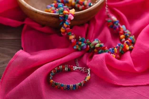 Bijouterie de gemmes ethniques posée sur un châle en soie rose