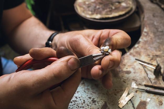 Un bijoutier démonte une bague en or avec des perles dans un atelier, gros plan