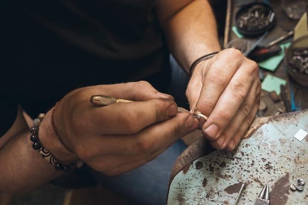 Un bijoutier démonte une bague en or avec des pierres dans un atelier, gros plan