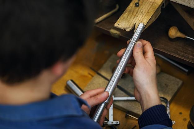 Le bijoutier détermine la taille de la bague sur un outil spécial appelé une jauge à anneau dans l'atelier
