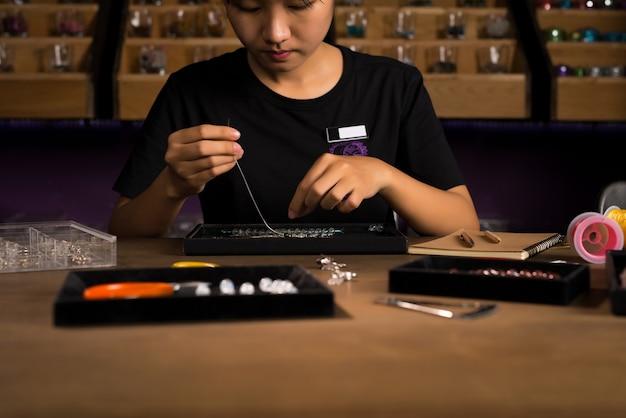 Bijoutier fabriquant des bijoux en perles de pierre faits à la main.
