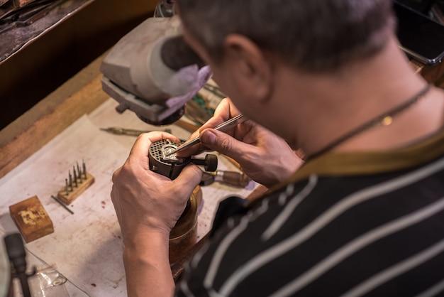 Un bijoutier fixe des pierres précieuses sur un pendentif en argent