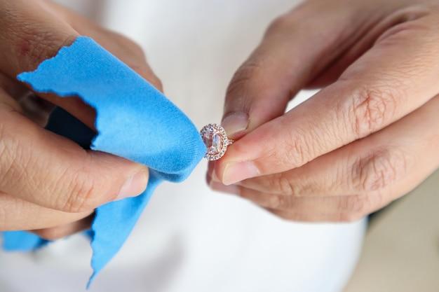 Bijoutier polissage à la main et nettoyage de la bague en diamant de bijoux avec tissu en microfibre