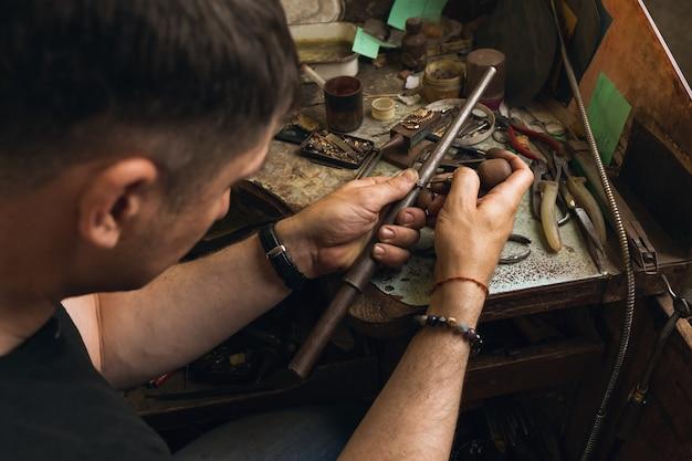 Un bijoutier répare une bague en or et diamants dans son atelier, processus de travail
