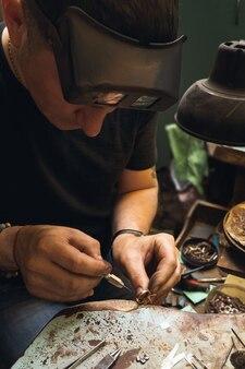 Le bijoutier répare les bijoux en or dans son atelier, examine la bague pour les défauts