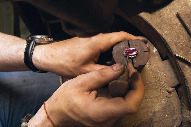 Le bijoutier répare la pierre dans le cadre d'une bague en or, gros plan