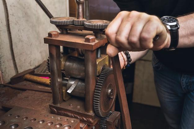 Un bijoutier roule une feuille de métal pour l'utiliser dans son travail