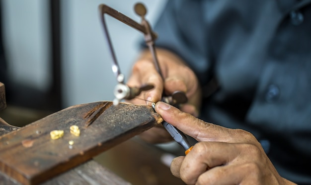 Bijoutier thaïlandais, gère les bijoux et les pierres précieuses dans l'atelier, le processus de fabrication de bijoux, gros plan