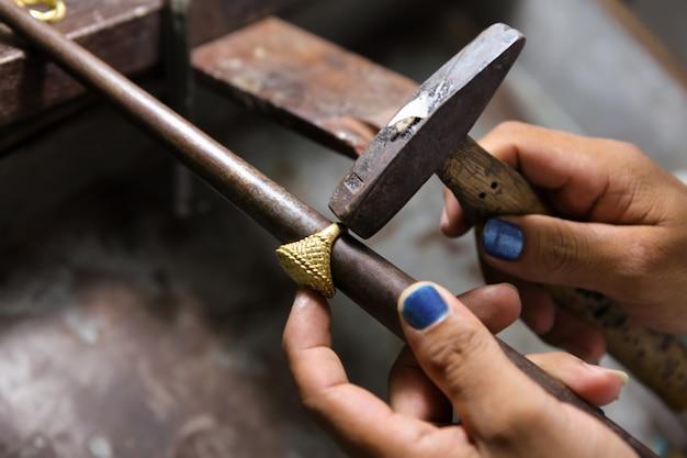 Bijoutier travaillant avec le marteau sur la bague en or dans son atelier