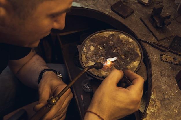 Un bijoutier utilise une torche pour faire fondre une pièce pour la réparation de bijoux