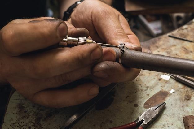 Un bijoutier vérifie la fixation d'une pierre précieuse dans une bague en or, gros plan