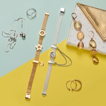 Bijoux en argent et or sur fond jaune et bleu minimal